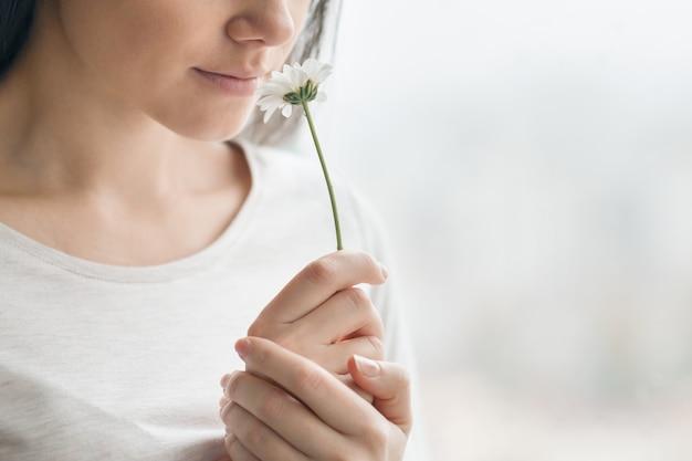 Closeup retrato de niña con flor de manzanilla