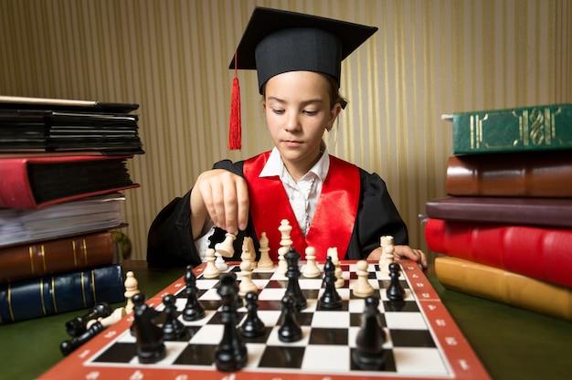 Closeup retrato de niña inteligente en gorro de graduación jugando al ajedrez