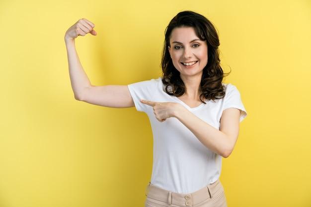 Closeup retrato de una niña mostrando fuertes músculos del brazo