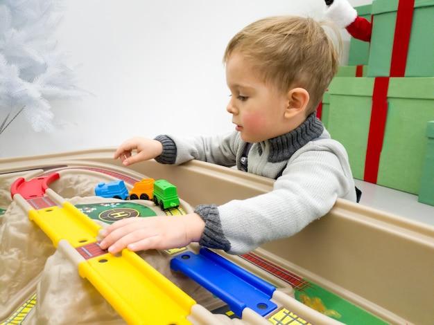 Closeup retrato de niño pequeño jugando con vías y trenes de juguete
