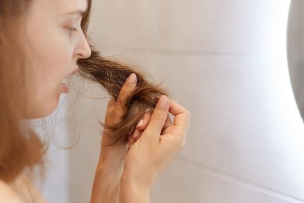Closeup retrato de perfil de mujer sorprendida molesta que mira su cabello seco, tiene problemas, necesita cambiar el champú o un tratamiento especial en la clínica tricológica.