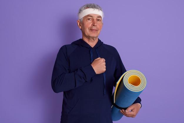 Closeup retrato de senior vestidos con capucha azul y banda para la cabeza blanca, manteniendo el puño en el pecho, sosteniendo la estera de yoga en las manos, fotografiándose después del ejercicio físico
