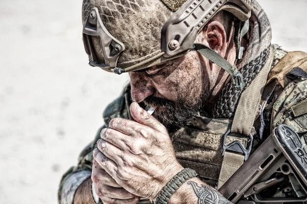 Closeup retrato de soldado de fumar en el desierto entre rocas