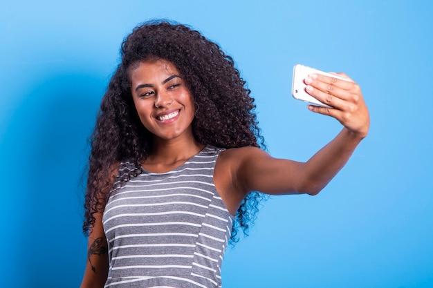 Closeup retrato de sonriente joven atractiva mujer brasileña africana sosteniendo smartphone, tomando selfie foto sobre fondo azul.