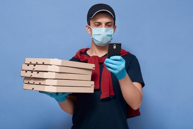 Closeup retrato de un tipo que trabaja como empleado de pizzería en línea, repartidor con pila de cajas de pizza y teléfono inteligente en las manos, intenta encontrar la dirección del cliente