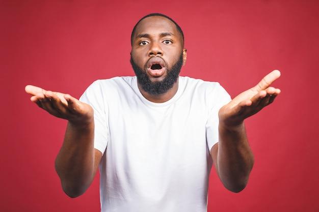 Closeup retrato de tonto joven africano despistado, brazos preguntando por qué cuál es el problema a quién le importa y qué