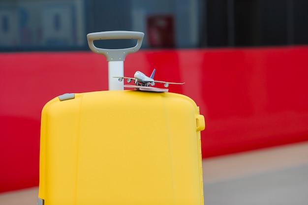 Closeup rojo pasaportes y avión modelo pequeño en equipaje amarillo en la estación de tren