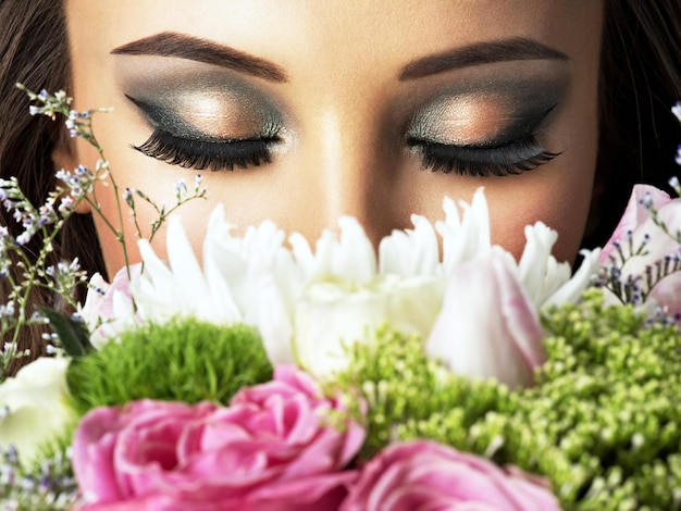 Closeup rostro de hermosa niña con flores. mujer atractiva joven sostiene el ramo de flores de primavera