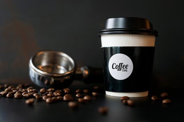 Closeup taza de papel y grano de café en la mesa negra