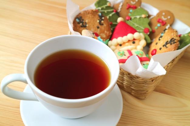 Closeup una taza de té caliente con borrosa cesta de galletas de navidad