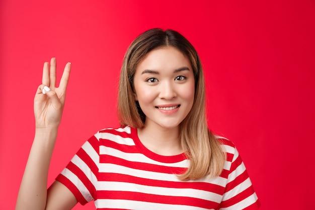 Closeup tierna amigable tonta joven asiática rubia novia sonriendo con dientes mostrar número tres dedos ...