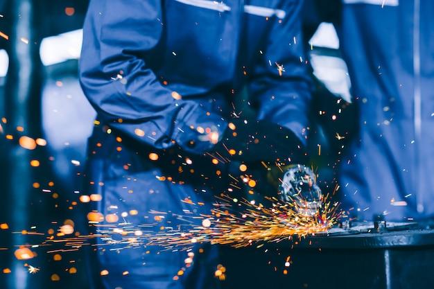 Closeup trabajador de acero pesado con disco de molienda de rueda eléctrica cortando placa de metal en el lugar de trabajo