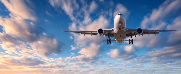 Cloudscape con avión de pasajeros blanco volando Foto Premium