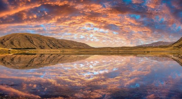 Cloudscape de colores vibrantes en ashburton lakes district con una impresionante puesta de sol reflejada en la superficie del agua