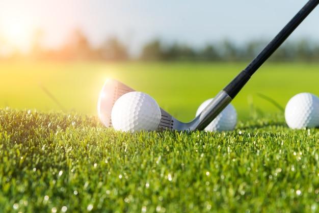 Club de golf y pelota en el césped y la puesta del sol