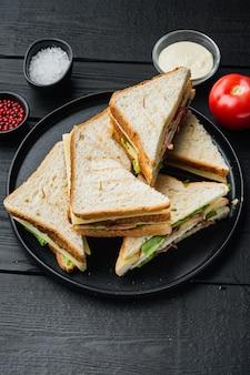 Club sándwich con carne, queso, tomate, jamón, sobre mesa de madera negra
