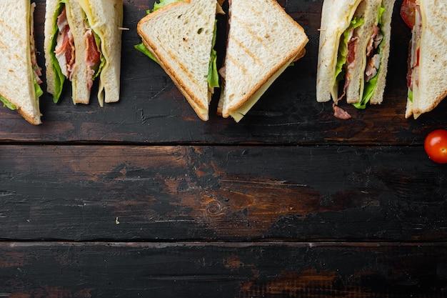 Club sándwich con carne, queso, tomate, jamón, sobre mesa de madera oscura, vista superior