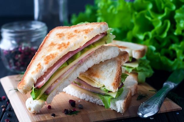Club sandwich con ensalada en plato de madera.