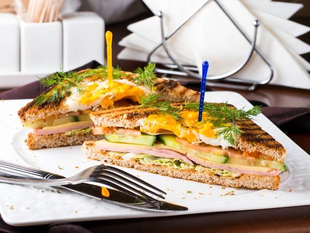 Club sandwich con huevo, pepino, tomate, jamón.