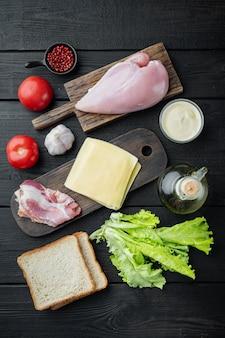 Club sándwich con ingredientes frescos, sobre fondo de madera negra, vista superior