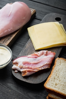 Club sándwich con ingredientes frescos, sobre mesa de madera negra