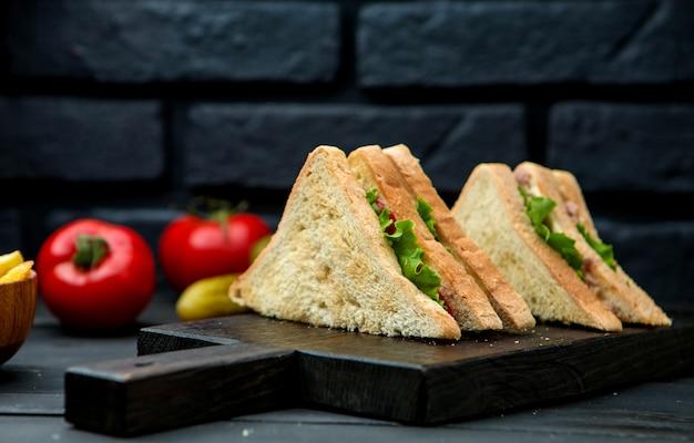 Club sandwich con pan crujiente sobre una plancha de madera