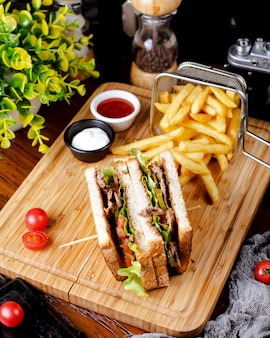 Club sandwich con papas fritas en la mesa