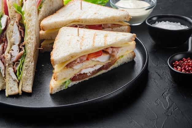 Club sándwich de pavo casero, sobre mesa negra