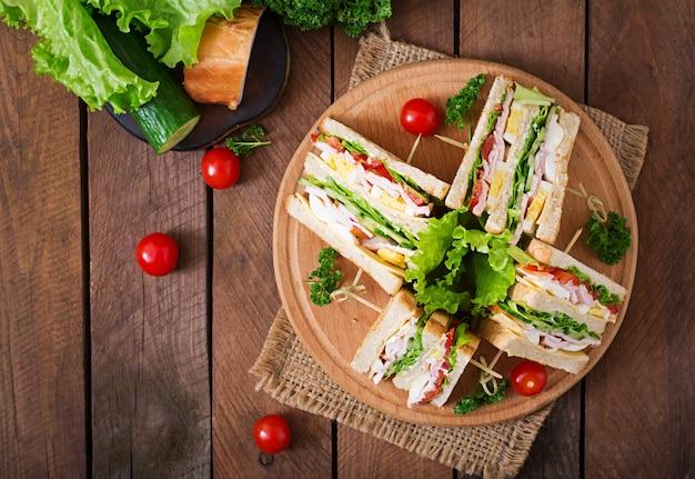 Club sandwich con queso, pepino, tomate, jamón y huevos. vista superior