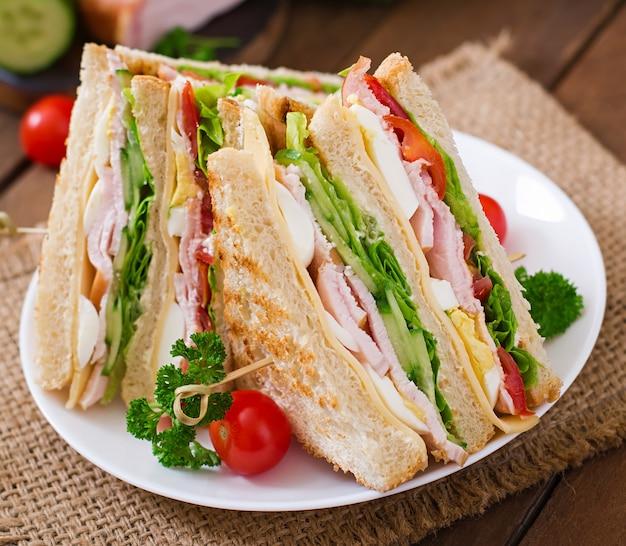 Club sandwich con queso, pepino, tomate, jamón y huevos.