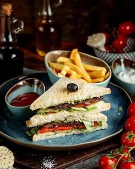 Club sanwich con papas fritas y salsa de tomate