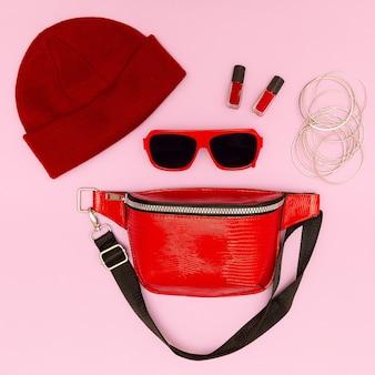 Clutch de moda, gafas de sol, joyas de oro. estilo hipster endecha plana. centrarse en rojo