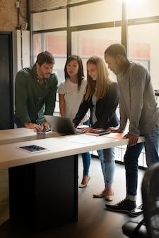 Co trabajadores de pie sobre el escritorio pasando por presentación en computadora