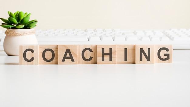 Coaching palabra hecha con bloques de madera. conceptos de vista frontal, planta verde en un florero y teclado blanco sobre fondo