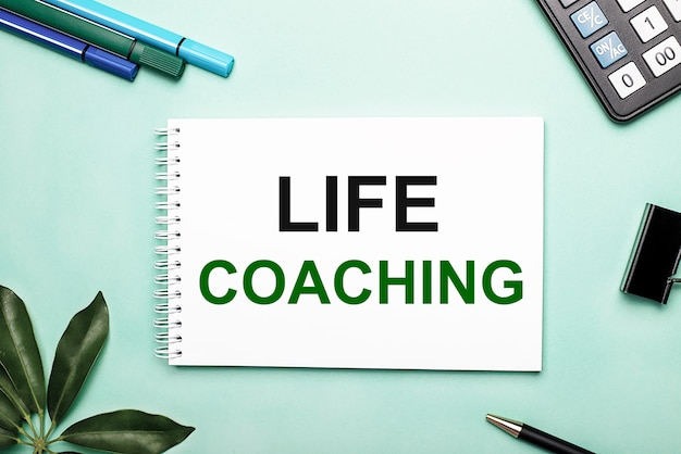 Coaching de vida está escrito en una hoja blanca sobre un fondo azul cerca de la papelería y la hoja de scheffler. llamada a la acción. concepto motivacional