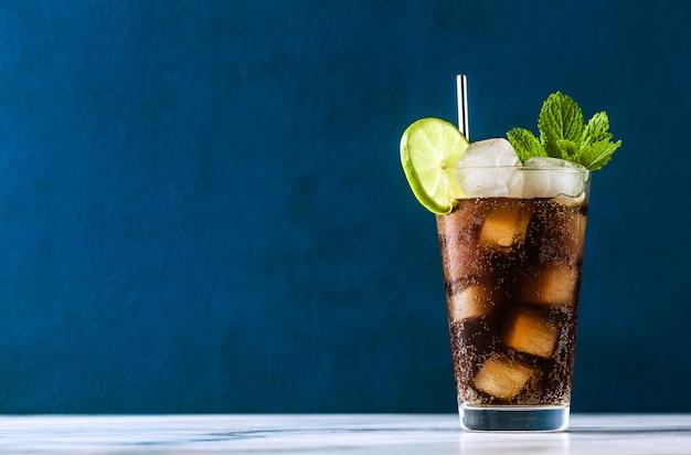 Coca-cola cóctel en un vaso alto cuba libre. refrescante bebida de verano