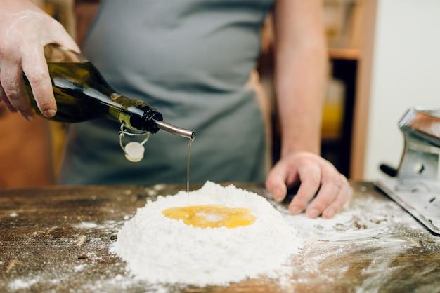 Cocción de pasta casera, el hombre agrega aceite a la harina en la mesa de la cocina de madera. cocina tradicional italiana
