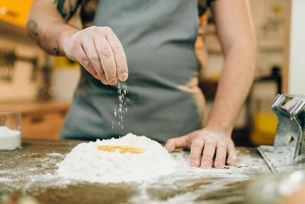 Cocción de pasta casera, hombre preparando masa. huevo y manojo de harina en la mesa de madera