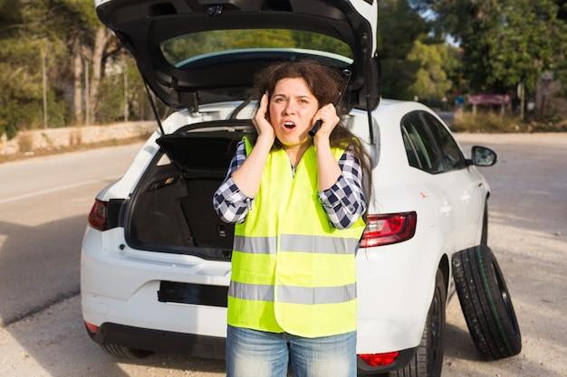 Coche averiado. mujer de pie junto a su coche averiado en la carretera esperando emergencias