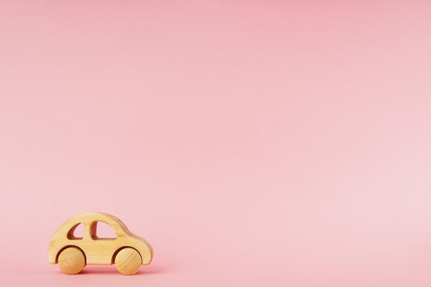 Coche de bebé de madera sobre un fondo rosa pastel con copyspace.