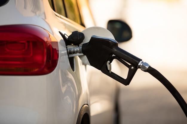 Coche blanco en la gasolinera se llena con combustible