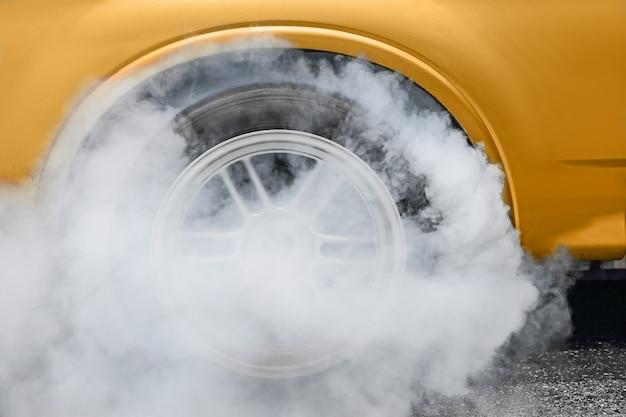 El coche de carreras de arrastre quema goma de sus neumáticos en preparación para la carrera