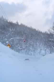 Coche en una carretera de montaña en un día nevado