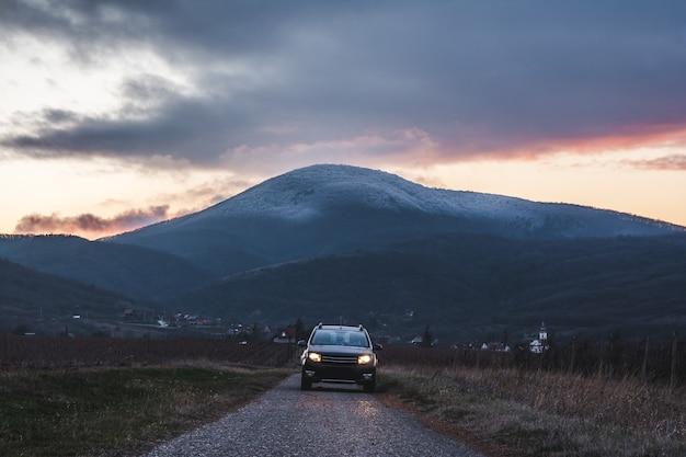 Coche en la carretera con una montaña durante la puesta de sol.