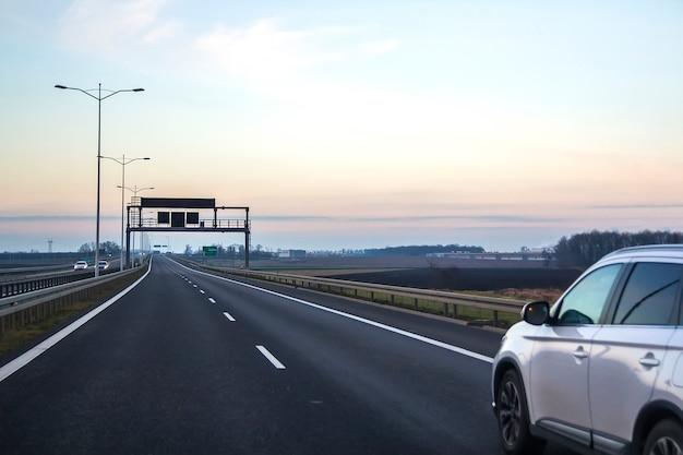 Coche en carretera con señales direccionales en blanco.