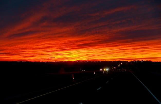 Coche en carretera temprano en la puesta del sol con amaneceres.
