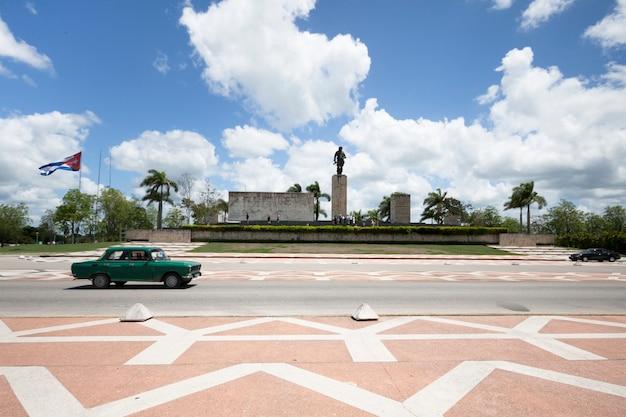 Coche de clasificación pasando frente a monumento en cuba