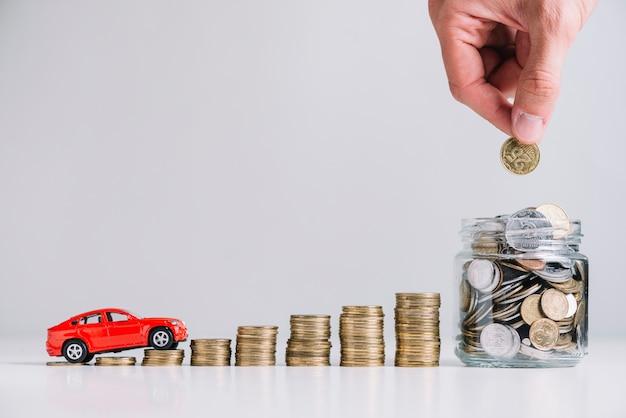 Coche conduciendo sobre el aumento de monedas apiladas cerca de la mano de la persona poniendo monedas en el tarro de cristal