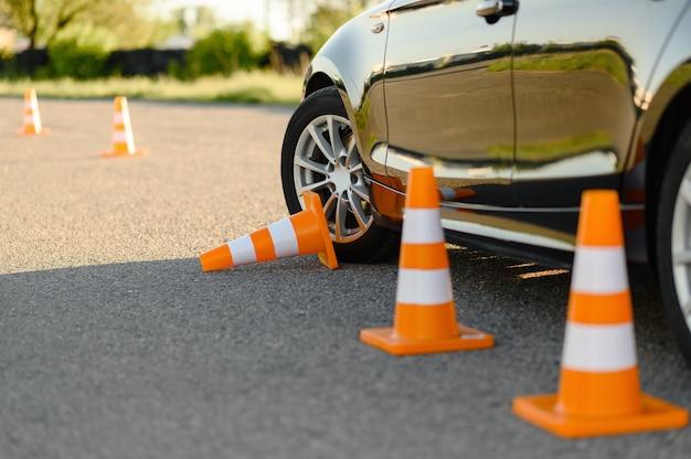 Coche y cono de tráfico derribado, lección de concepto de escuela de conducción.