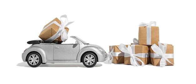 Coche convertible plateado con un regalo para las vacaciones sobre un fondo blanco aislado. concepto de navidad y año nuevo